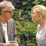 Scarlett Johansson wearing glasses and her hair in a ponytail talking to Woody Allen, who is wearing a gray suit