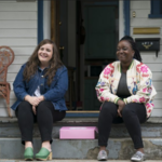 Aidy Bryant and costar Lolly Adefope sit on the steps of a house