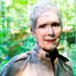 E. Jean Carroll, an older white woman with short, gray hair, stands in a forest in a gray trench coat