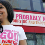 an Indian woman wears a pink t-shirt that says there is no God