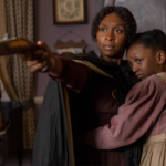 Cynthia Erivo, a Black British woman, portrays Harriet Tubman, a darkskinned Black woman dressed in a brown outfit and holding a gun in her land with a Black child in her right arm