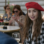Lily Collins as Emily in Emily in Paris. Emily is a white girl with long brown hair. She wears a red beret and looks surprised while sitting at a brunch table outside.