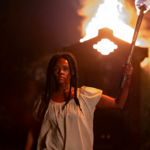 Janelle Monáe plays Veronica, a Black woman with short, black hair, holding a torch in a dark field, in Antebellum