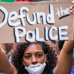 A Black woman with short, black curly hair holds a cardboard sign that says Defund the Police as she walks across the Brooklyn Bridge