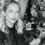 Tessa Miller, a white woman with short blond hair, poses in a black and white photo with her small, brown dog