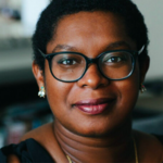Ashley C. Ford is a brown-skinned Black woman with a short black afro and glasses