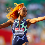 Sha'Carri Richardson, a dark-skinned Black woman with long, orange hair, runs at top speed as she points toward the audience