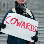 "a white man, Alan Gambrell, holds a sign that says the word ""coward"" outside of the U.S. Capitol"