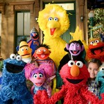 characters on Sesame Street, including Bert, Ernie, and Big Bird, stand on the street together
