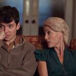 Actor Asa Butterfield, a young white man with brown hair and an embarrassed look, sits next to Gillian Anderson, a white woman with short, blond hair, sit on a couch.