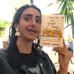 "A selfie of author and illustrator Shelby Lorman, who is white with dark hair. She holds up her book, ""Awards for Good Boys."""