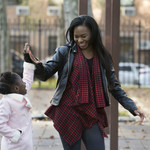 a Black mother and her Black daughter exchange high-fives and smile at each other in a park