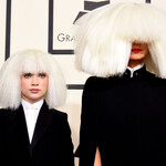 One white teen girl and one white woman wear oversized white wigs with massive bangs that hang over their eyes.