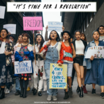 a group of students, many of whom are Asian, walk together during a protest, carrying signs that read WhoMadeYourClothes and It's Time for a Revolution