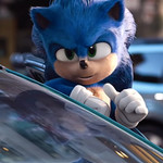 Sonic, a blue animated hedgehog with large eyes, peeks out from an open car door.