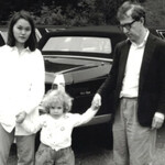 a black and white photo captures Soon-Yi Previn, an Asian American teen, holding hands with Dylan Farrow, a small, white child, and Woody Allen, an aging white man with glasses