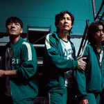 Still photo of three wary-looking figures in green track suits