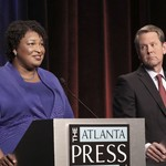 a Black woman with short brown locs standing next to a white man on a debate podium