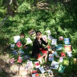 Stephanie Camba sits in the shadows of a tree in the grass, surrounded by books.