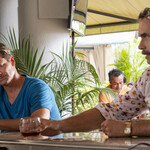 Steve Zahn as Mark, a distraught white man sitting at the bar beside iMurray Bartlett as Armond, a white man wearing a colorful shirt, in The White Lotus