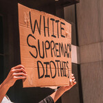 "A protest sign reading ""White supremacy did this."""