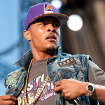 "T.I. is wearing a purple snapback hat, a grey t-shirt with purple writing, and a denim vest that says ""Akon"""