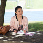 Asian teenager with Black hair pulled in a ponytail sitting at an outdoor lunch table