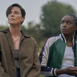 "Nile, a young Black woman with braids, and Andy, a white woman with short dark hair, lean on a car in ""The Old Guard."""
