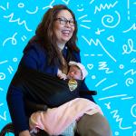Tammy Duckworth in her wheelchair holding her daughter