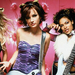 Three women in a pop punk band wearing cat ears posing with instruments.
