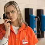 an incarcerated white woman with blond hair talks on the phone