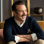 Jason Sudeikis as Ted Lasso, an aging white man with short, brown hair and a blue sweater, in Ted Lasso