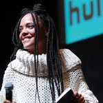 Tessa Thompson onstage holding a microphone