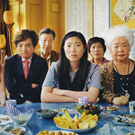 Awkwafina sitting at a dinner table with her entire family, looking conflicted
