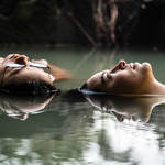 Two girls float in a pond on their backs, the camera up close to their faces.