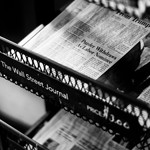 """Black and white image of newspapers on a black rack labeled """"The Wall Street Journal"""""""