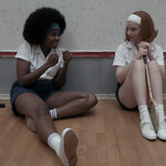 Two young women sit next to each other while dressed for tennis. One is a Black girl with an afro and dark skin, and the other is pale with red hair.