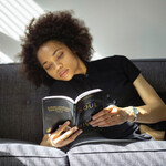 a light-skinned Black woman with a short afro reads a book while sitting on the couch