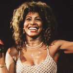 Tina Turner, a Black woman wearing a blond wig, smiles brightly while performing on stage