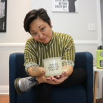 Traci Medeiros-Bagan, an Asian therapist with short black hair, sits cross-legged and holds a coffee mug toward the camera