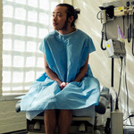 a genderqueer person sitting in a hospital gown sitting in an exam room
