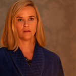 Reese Witherspoon plays Elena, a white woman with a short, blond bob, who is looking at a fire in a room in Little Fires Everywhere