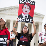 Protesters in front of the Supreme Court stand against Brett Kavanaugh with signs.