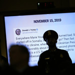 a police officer stands in shadow in front a projector with a tweet from Donald Trump about Marie Yovanovitch