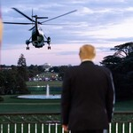 Donald Trump, a white dumpy man, stands behind a gate as he looks at a helicopter take off