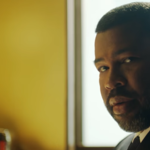 A closeup of Jordan Peele wearing a suit and staring into the camera, a yellow wall behind him
