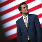 U.S. Congressman Matt Gaetz in a blue suit and yellow tie posing in front of an American flag