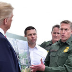 Donald Trump's back is turned to the camera as he speaks to several men in green uniforms with U.S. Border Patrol badges on them