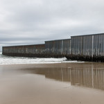 Mexico-U.S. border divided by a barrier of steel slats that end in the Pacific ocean