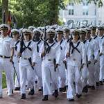 Naval cadets wearing white uniforms and marching in formation at the U.S. Naval Academy